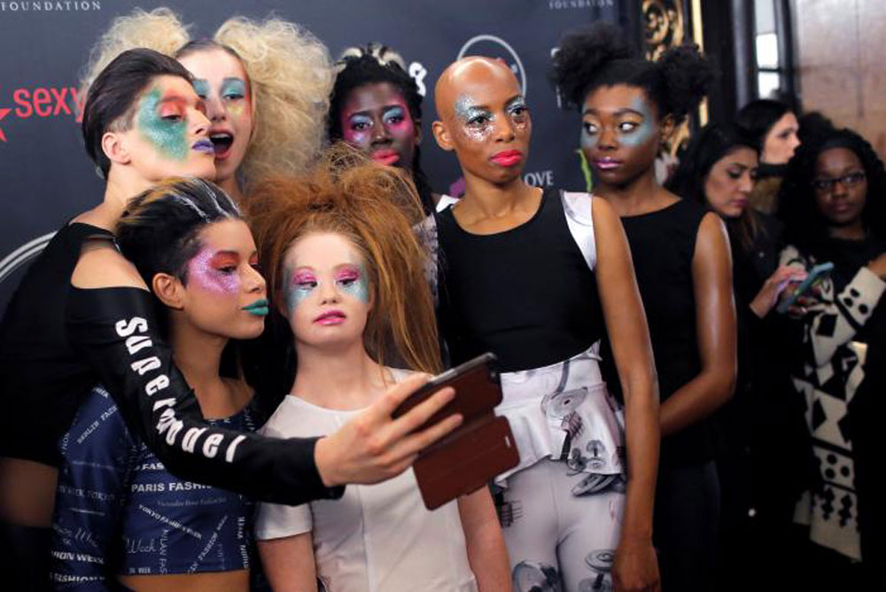 The young designer poses with her models backstage (photo c/o AFP)